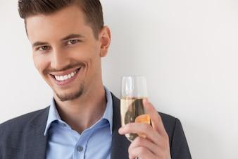 Primer del hombre joven sonriente con vaso de vino