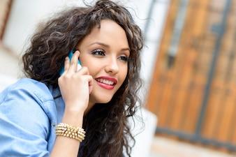 Primer plano de adolescente con el pelo rizado hablando por teléfono