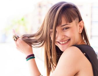 Primer plano de adolescente sonriente jugando con su pelo