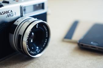 Primer plano de cámara clásica con teléfono borroso de fondo