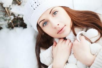 Primer plano de chica con gorro de lana tumbada en el suelo
