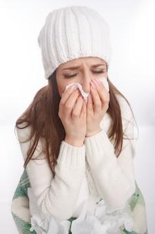Primer plano de chica enferma sonándose la nariz