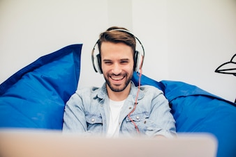 Primer plano de chico feliz usando auriculares