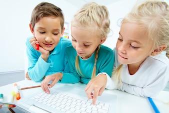 Primer plano de compañeros de clase jugando con el ordenador