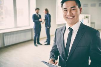 Primer plano de ejecutivo seguro con empresarios de fondo