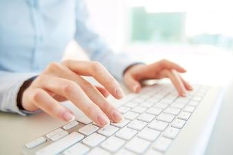 Primer plano de empleada con el teclado del ordenador