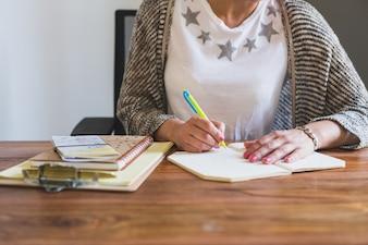 Primer plano de empleada escribiendo en una libreta