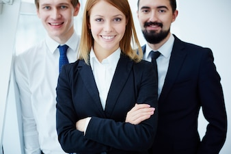 Primer plano de empresaria orgullosa con compañeros detrás