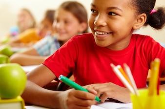 Primer plano de estudiante sonriente con sus compañeros de fondo