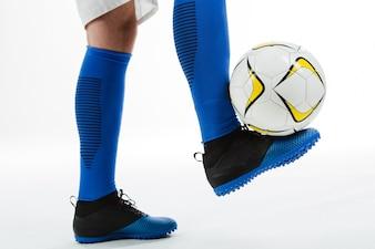 Primer plano de futbolista con balón en el pie