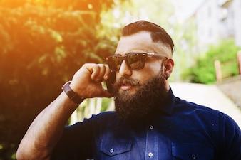Primer plano de hombre con barba hablando por teléfono