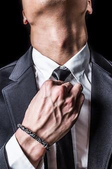 Primer plano de hombre de negocios arreglando su corbata