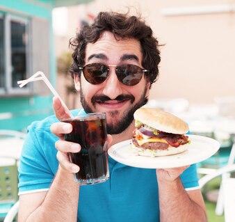Primer plano de hombre disfrutando de su hamburguesa y refresco
