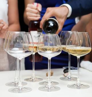 Primer plano de hombre vertiendo vino blanco