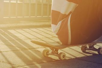 Primer plano de joven adolescente tener descanso o sentarse en un parque de patinaje en día de verano al aire libre, vista lateral. Área urbana. Viraje.