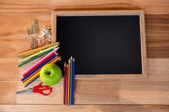 Primer plano de la pizarra con lápices de colores y manzana