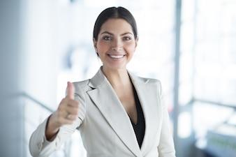 Primer plano de la señora feliz de negocios mostrando el pulgar hacia arriba