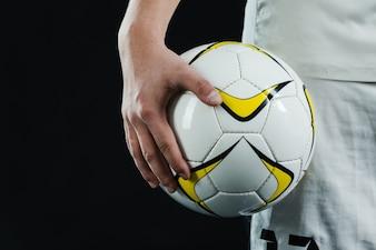 Primer plano de mano sujetando un balón de fútbol