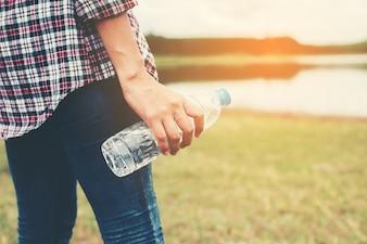 Primer plano de mano sujetando una botella de plástico