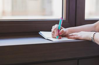 Primer plano de manos con bolígrafo escribiendo en una libreta