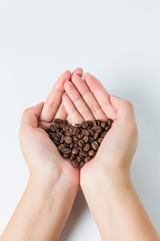 Primer plano de manos con granos de café