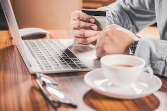 Primer plano de manos de hombre con tarjeta de crédito para compra online