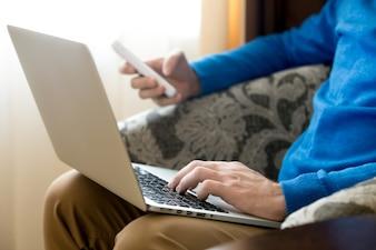 Primer plano de manos de hombre usando un portátil y un móvil