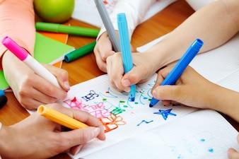 Primer plano de manos pintando un cuaderno