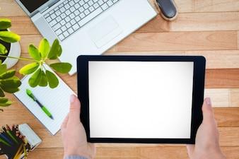 Primer plano de manos sujetando una tableta con portátil de fondo