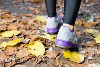 Primer plano de mujer caminando con zapatillas de deporte