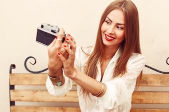 Primer plano de mujer con camiseta blanca tomándose una foto