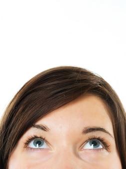Primer plano de mujer con ojos azules mirando hacia arriba