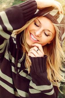Primer plano de mujer con una gran sonrisa llevando un jersey de rayas