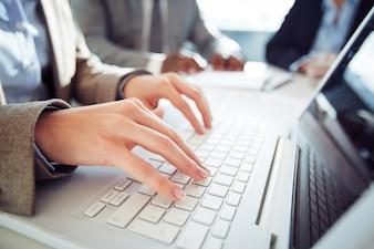 Primer plano de mujer de negocios escribiendo en el teclado de ordenador