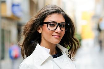 Primer plano de mujer encantadora con gafas y el pelo largo