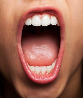 Primer plano de mujer joven enseñando los dientes y la lengua