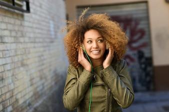 Primer plano de mujer joven llevando una chaqueta verde y escuchando música