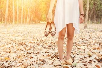 Primer plano de mujer llevando sus zapatos en la mano