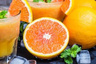 Primer plano de naranja sabrosa con vasos de fondo