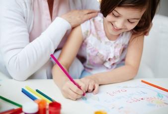 Primer plano de niña pequeña dibujando con su madre