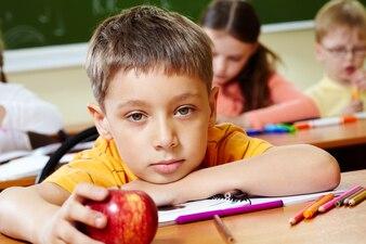 Primer plano de niño aburrido con una manzana