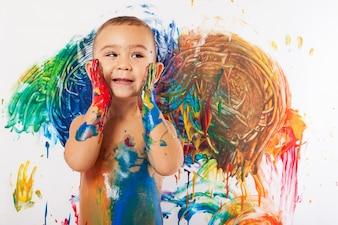 Primer plano de niño encantador lleno de pintura