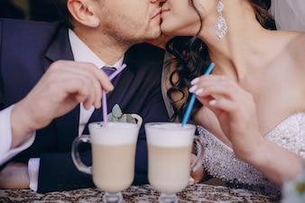Primer plano de recién casados con unas bebidas
