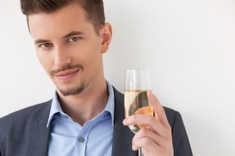 Primer plano de Relajado hombre joven que sostiene una copa de vino