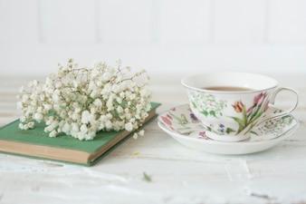 Primer plano de taza café, flores y libro