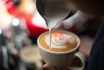 Primer plano de taza de café con una flor de espuma