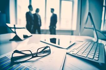 Primer plano de teclado y gafas con ejecutivos de fondo