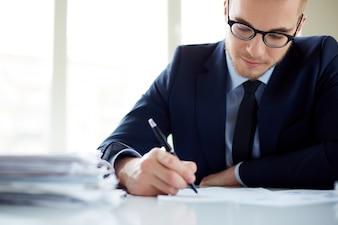 Primer plano de trabajador escribiendo un informe