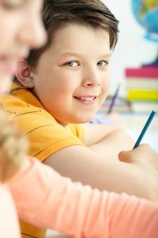 Primer plano de un niño sonriendo con un lápiz