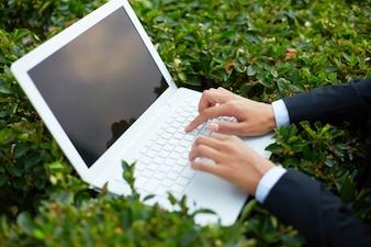 Primer plano de un portátil en un arbusto